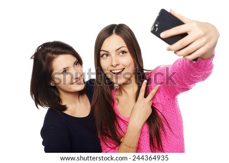 Two girls friends taking selfie with smartphone, isolated on white background - stock photo
