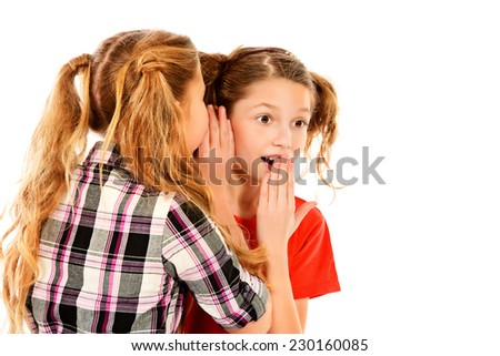 Two girls friends talking about their secret. Isolated over white.