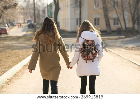 Two girls girlfriend, or mother and daughter are on the road hand in hand with fashionable backpack walking along the road - stock photo