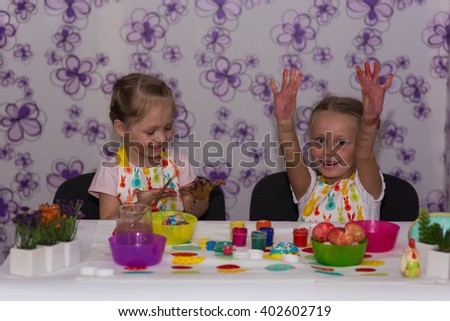 Two girls girlfriends paint painted hands and play their hands  - stock photo
