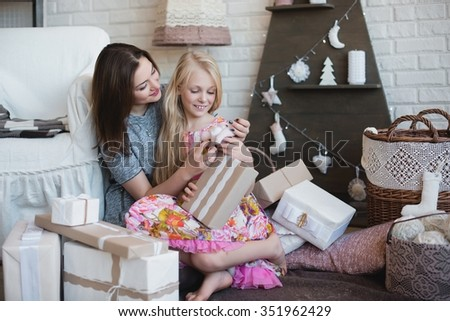 Two girls give each other gifts, hugs, preparation for Christmas, decoration, decor, lifestyle, family, family values