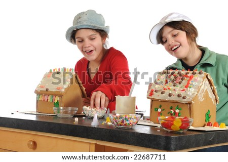 Two girls happily decorating gingerbread houses with an assortment of colorful candies.  Isolated on white. - stock photo
