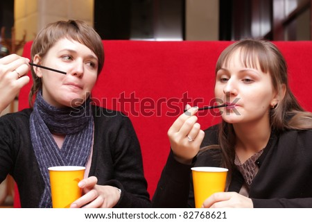 Two girls have a cup of coffee at cafe - stock photo