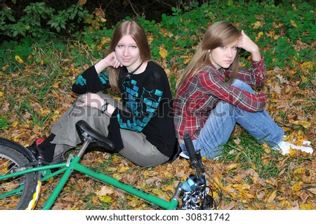 Two girls have rest in autumn forest - stock photo