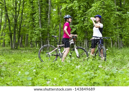 two girls having a break during cycling  in the forest - stock photo