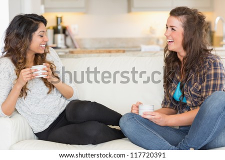 Two girls having coffee and laughing on sofa - stock photo