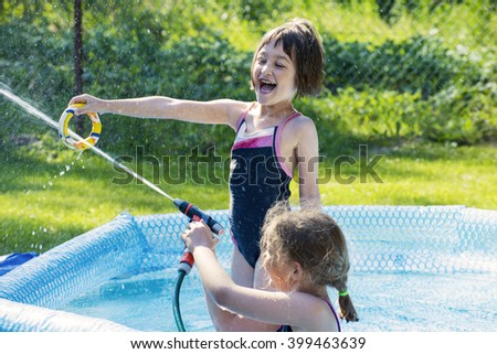 Two girls having fun in pool outdoor while playing with water hose. - stock photo