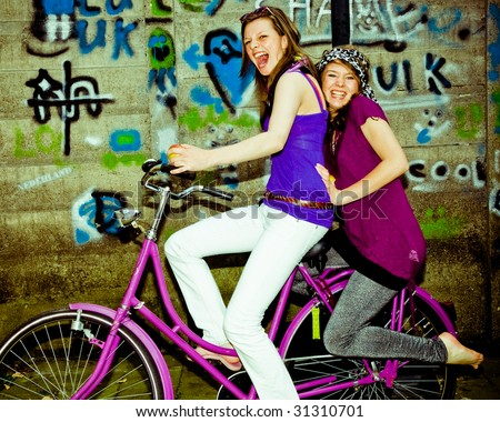 two girls having fun on a bicycle, personal editing ,green toning - stock photo