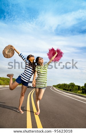 two girls having fun on the road trip at summertime - stock photo