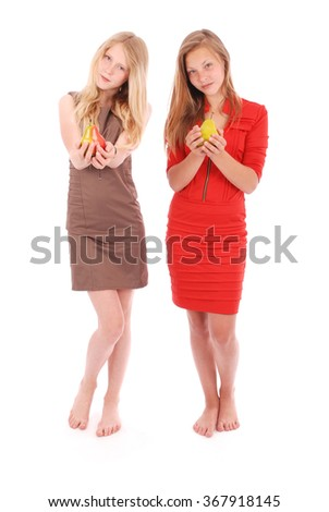 Two girls holding fresh pear isolated on white - stock photo