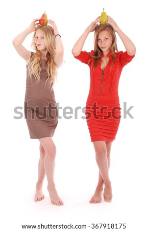 Two girls holding fresh pear on her head, isolated on white - stock photo
