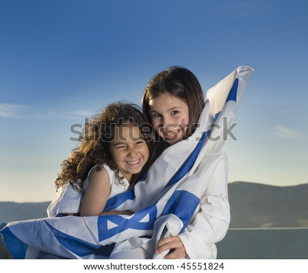 two girls holding hugging the Israeli flag - stock photo