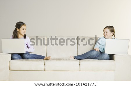 Two girls holding laptops on sofa