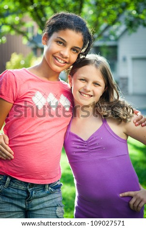 Two girls hug outdoors in the sunshine. - stock photo