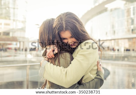 Two girls hugging each others after long time they have been distant - stock photo