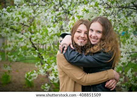 Two girls hugging in the park, two women girlfriend in the spring. two girls on a background of flowering trees  - stock photo
