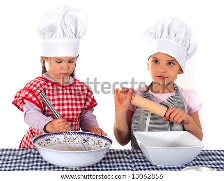 Two girls in aprons and chef's hats making a cake