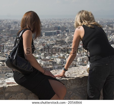 Two girls in black gaze at the city of Athens from the Acropolis wall - stock photo
