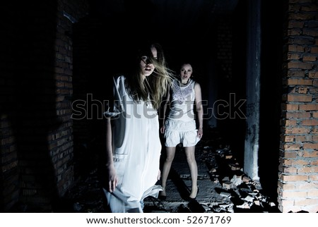 Two girls in dark building ruins - stock photo