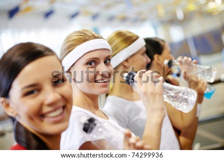 Two girls in gym taking break and drink - stock photo