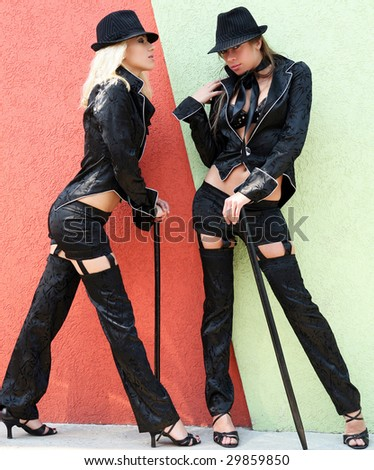 Two girls in male suit with walking stick.