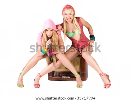 Two girls in microphone singing - stock photo