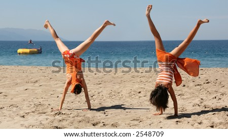 Two girls in orange clothes doing cartwheel on the beach - stock photo