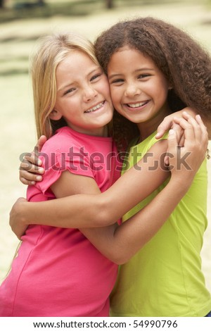 Two Girls In Park Giving Each Other Hug - stock photo