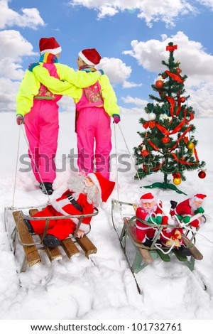 Two girls in Santa Claus cap pulling Santos on a sled  (concept:winter fun) - stock photo