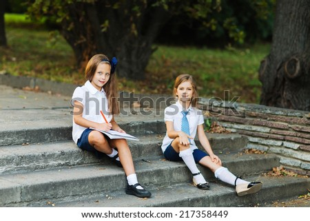 Two girls in school uniform  studying at the park - stock photo