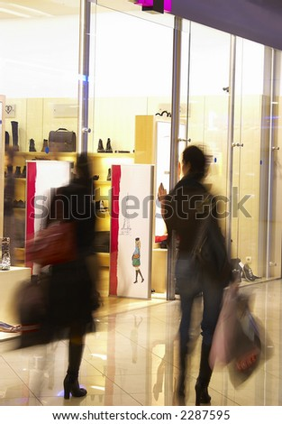 Two girls in shopping center near a show-window of shop. - stock photo