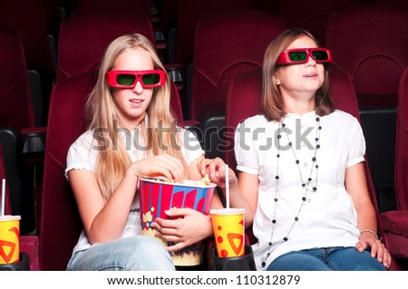 Two girls in the cinema watching the three-dimensional movie to have fun - stock photo