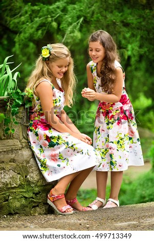 Two girls in the same bright dresses in the old Park