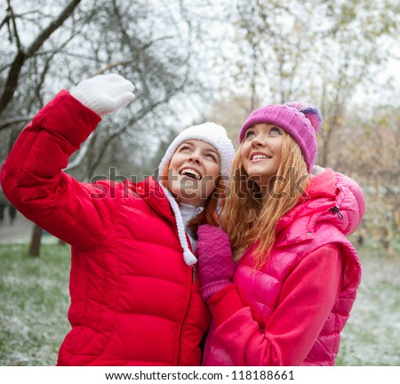 Two girls in the snow-covered park looking up and smiling - stock photo