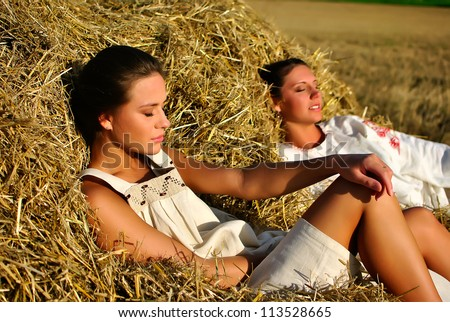 two girls in traditional Russian costume resting on a haystack - stock photo
