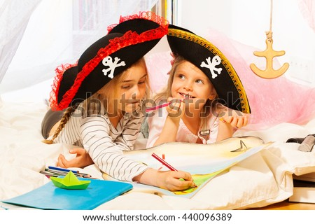 Two girls in tricorns drawing the treasure map - stock photo