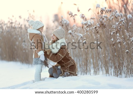 Two girls in warm clothes walking in a winter park smile at each other. Christmas. New Year - stock photo