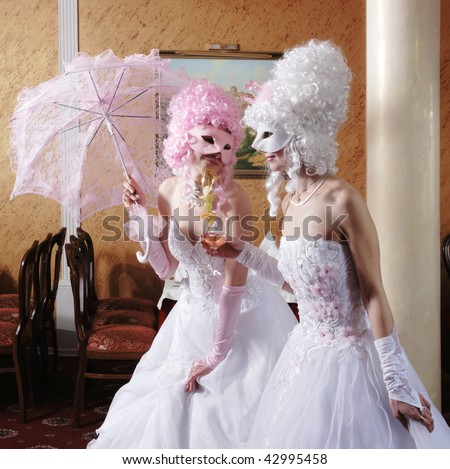 Two girls in wedding dresses and masks - stock photo