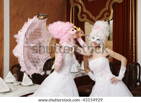 Two girls in wedding dresses and masks