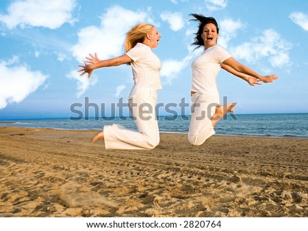 two girls jumping at the beach
