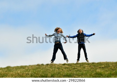 two girls jumping on a hilltop - stock photo