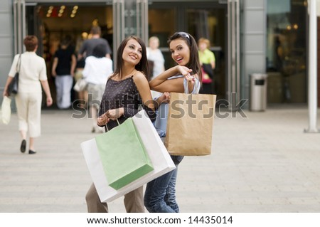 two girls just outside of commercial center with her purchases in bags