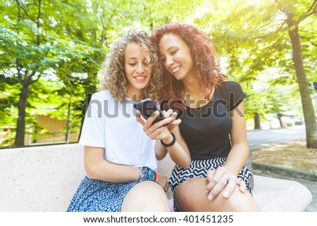 Two girls looking at smart phone. A couple of friends is sitting on a bench at park. They are smiling and having fun together looking at their smartphone. Technology and lifestyle concepts. - stock photo