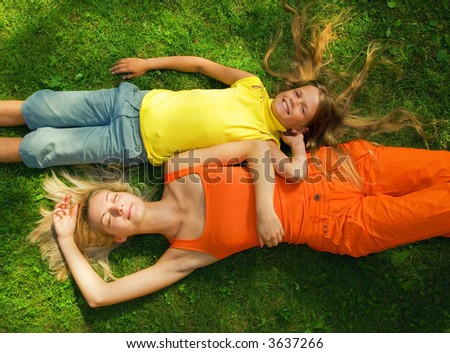 Two girls lying on a meadow - stock photo