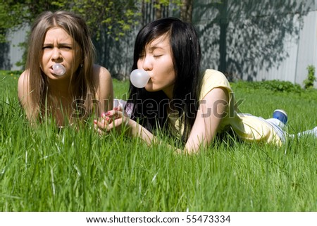 Two girls lying on grass - stock photo