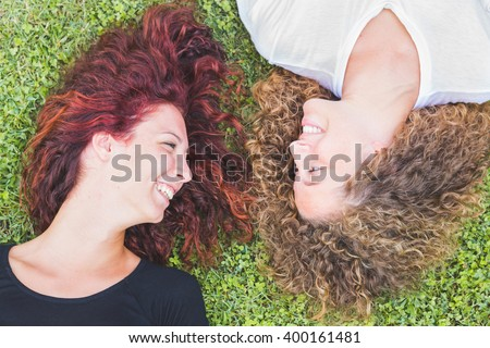 Two girls lying on the grass and looking each other smiling. They have curly hair and seems to be very happy. Friendship and lifestyle concepts.