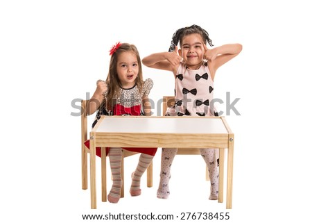 Two girls making funny faces and gesturing together isolated on white background - stock photo