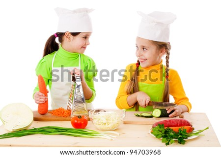 Two girls making salad, cooking the vegetables. Isolated on white