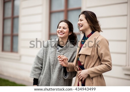 Two girls meet on the sidewalk. Feel joyfull and happy together.