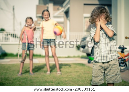 two girls mock at the little boy - stock photo